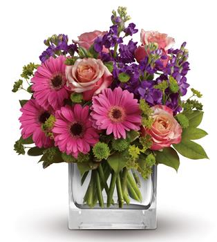 Called: Sweet Promises. Description: Like the dawn of a fine spring day, this pretty pink gift of gerberas, roses and delicate blue delphinium promises happiness!