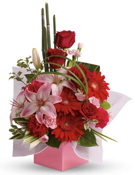 Called: Artistic Expression. Description: The art of love. Take their breath away with this uniquely sculptural arrangement of lilies, gerberas and canes of bamboo-like equisetum.