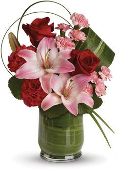 Called: Delicate Dance. Description: This gorgeous arrangement delivers the spirit of adventure. It is a unique mix of red roses, pink lilies, leaves and lily grass arranged in a chic leaf lined vase.