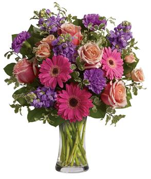 Called: Pure Bliss. Description: Give the gift of pure bliss! Lush, lavish and luxurious, this beautiful bouquet of roses, gerberas, stock and carnations in a vase is an instant mood enhancer.