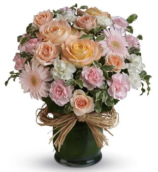 Called: She is Lovely. Description: Indeed she is! Show her with this soft symphony of feminine blooms, including roses, gerberas and carnations in a raffia lined vase.