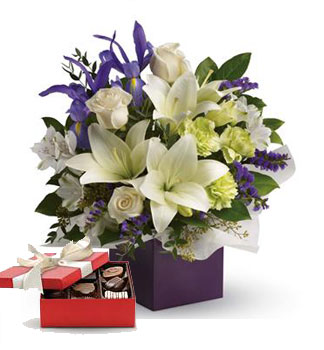 Called: Graceful Beauty. Description: Gorgeous white lilies and delicate blue iris dance gracefully with roses and alstroemeria in this luxurious arrangement.