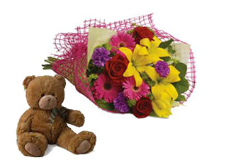 Called: Fun in the Sun. Description: Let the sun shine in with this exuberant bouquet of golden lilies, rich red roses and hot pink gerberas.