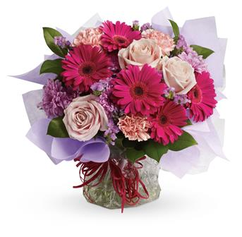 Called: Sweet Dreams. Description: Treat them to a special surprise! Hot pink gerbera mix with pale pink roses and carnations in this delightfully delicious bouquet.