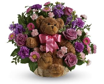 Called: Cuddles for Her. Description: Welcome the new bundle of joy to the family with this basket arrangement of lavender and pink blooms and a delightful bear.