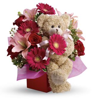 Called: Stylish Celebration. Description: Send a smile and a hug with this stylish mixed arrangement of hot pinks and reds accented with a snuggly bear that everyone will want to hold. Simply charming!
