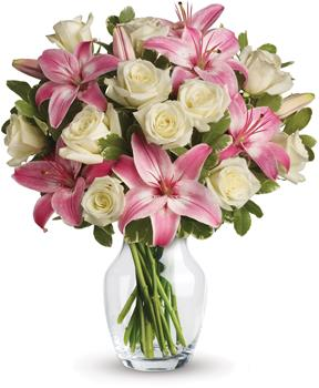 Called: Always a Lady. Description: A romantic gift like this one is always appreciated. An eye catching display of roses and lilies is perfectly arranged in a clear vase which makes a beautiful and lasting impression.