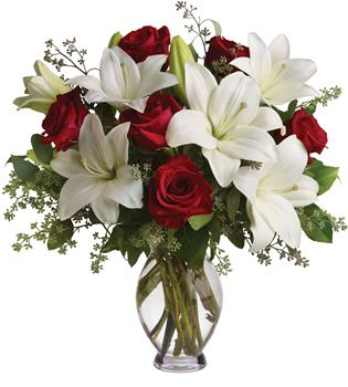 Called: Hooray for Love. Description: Put these words into flowers with this magnificent arrangement of red roses and white lilies accented with fresh greenery delivered in a classic clear glass vase.