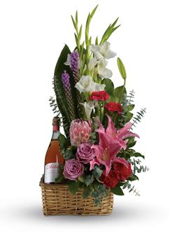 Called: Blushing Celebration. Description: Go all out for your special someone with this opulently awesome array of lavish flowers and sparkling wine, hand arranged in a wicker basket. It is an absolutely irresistible gift.