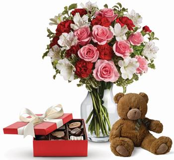 Called: It Looks Like Love. Description: Send this beautiful gift set including a delicious box of chocolates and delightful bear paired with a vase arrangement of light red and pink blooms.