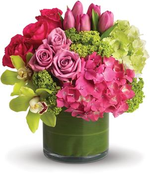 Called: Floral Fantasy. Description: Upscale and uptown. This fantastic arrangement is a beauty and a half to behold. Overflowing with gorgeous blossoms and delivered in a leaf-lined cylinder vase, it is truly a floral fantasy.