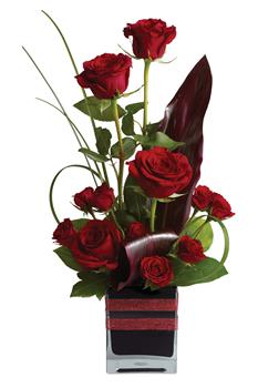 Called: Rose Romance. Description: Roses, the traditional flower of love, receive a modern twist in this imaginative arrangement, stylishly presented in a contemporary glass cube.