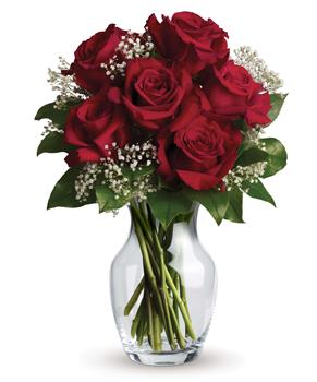 Called: Hearts Delight. Description: What a delight! Six stunning roses put your love centre stage in this charming vase arrangement.