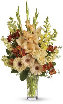 Called: Summers Light. Description: Express your condolences in tasteful shades of colour with peach, orange and yellow flowers in a clear glass vase. For the service or the home, it is an elegant choice.