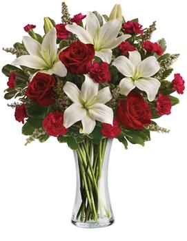 Called: Infinite Love. Description: Timeless romantic red roses and fragrant white lilies in a classic glass vase - a sweet yet spectacular way to express what is in your heart.