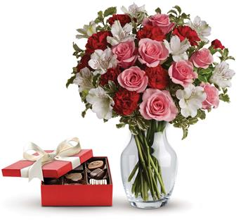Called: Eternal Love. Description: This charming gift set includes a delicious box of chocolates paired with a vase arrangement of light pink spray roses, red miniature carnations and white alstroemeria accented with assorted greenery.
