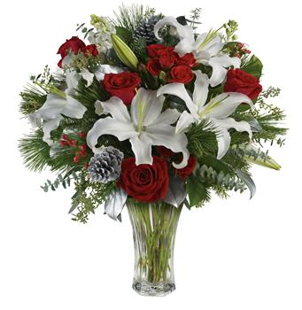 Called: Christmas Delight. Description: Take your gift-giving to new heights with this dramatic arrangement! Classic red roses, snowy lilies and naturally festive berries are presented in a complementing vase.