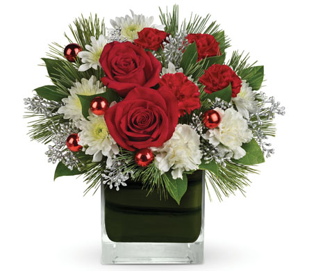 Called: Christmas Glitter. Description: Christmas glam! Accents of silver captivate beneath this lush Christmas arrangement of rich red roses nestled amongst snow white blooms.