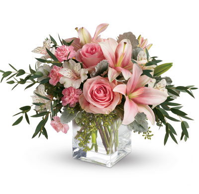 Called: Pink Flora. Description: Just fabulous! From its perky vase and perfect pink roses, to its textural greens and dramatic pink lilies, this chic bouquet is flora at its finest!